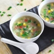 Sweet Corn Soup on a white bowl with soup spoon and garnished with some spring onions |