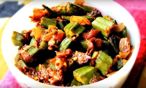 Bhindi Do Pyaza on a white bowl putted on a red handkerchief on light surface|