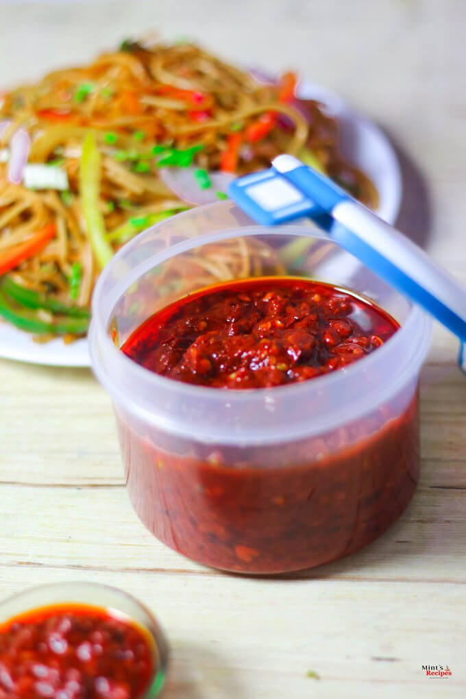Schezwan Sauce on a airtight container with a plate of noodles on it kept on a wooden surface |