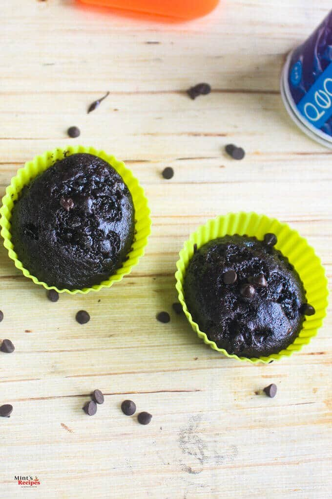 Eggless chocolate cupcake in a silicon mould with some choco chips sprinkles all over it on a wooden surface with a bottle behind |