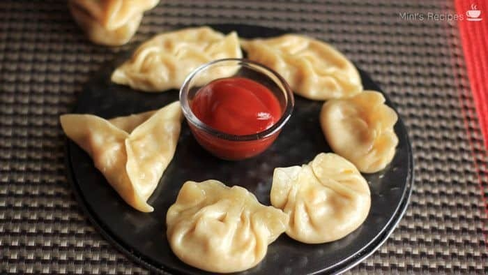 Veg momos on a white plate with some red chilli sauce in the center with a grey surface in background  