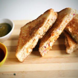 Veg Curd Sandwich on a wooden surface with some green chutney and tomato sauce