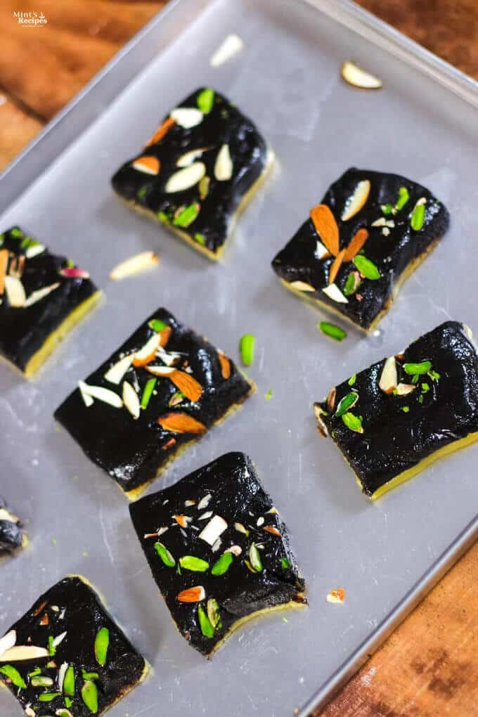 Chocolate Barfi on a steel tray with some pieces of chocolate khoya barfi with some garnishing of pista, and almonds kept on a wooden surface  