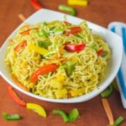 Masala maggi on a white bowl with lots of veggies spreaded around the bowl and a fork in it with a handkerchief on the side of the bowl |