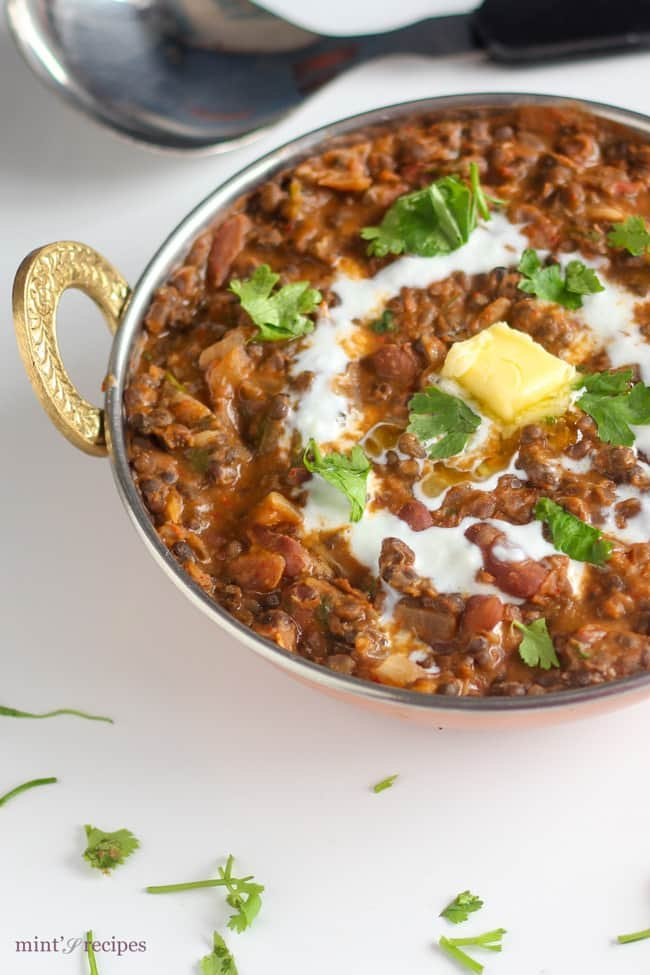 Dal Makhani on a deep heavy pan on a white surface. garnished with butter and cream with some coriander leaves