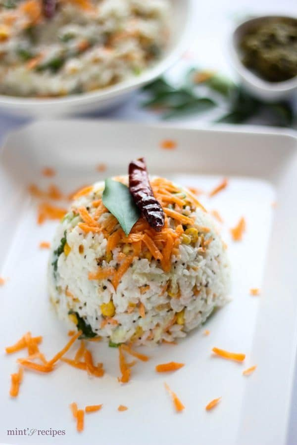 Curd Rice on a white tray with some grated carrot