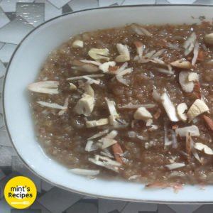 Meetha daliya on a white plate with lots of chopped cashew and almonds in it