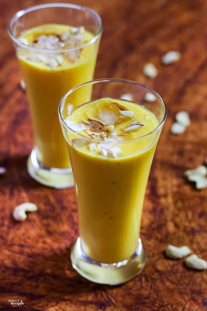 Mango Banana Smoothie on a glass with mango smoothie with some ice cubes, garnished with some cashew, almonds and saffron |