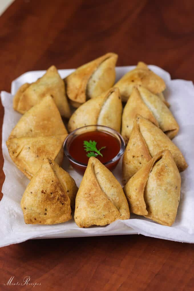 Samosa on a white tray with some tissue paper and little tomato ketchup on the center of the plate with rounded into samosas kept on a dark wooden surface |