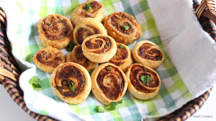 Pinwheel Samosa on a basket with a handkerchief on it and garnished with some chopped coriander leaves on the pinwheel samosas |