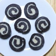 Chocolate Swiss Rolls on a white plate decorated round kept on a wooden surface|