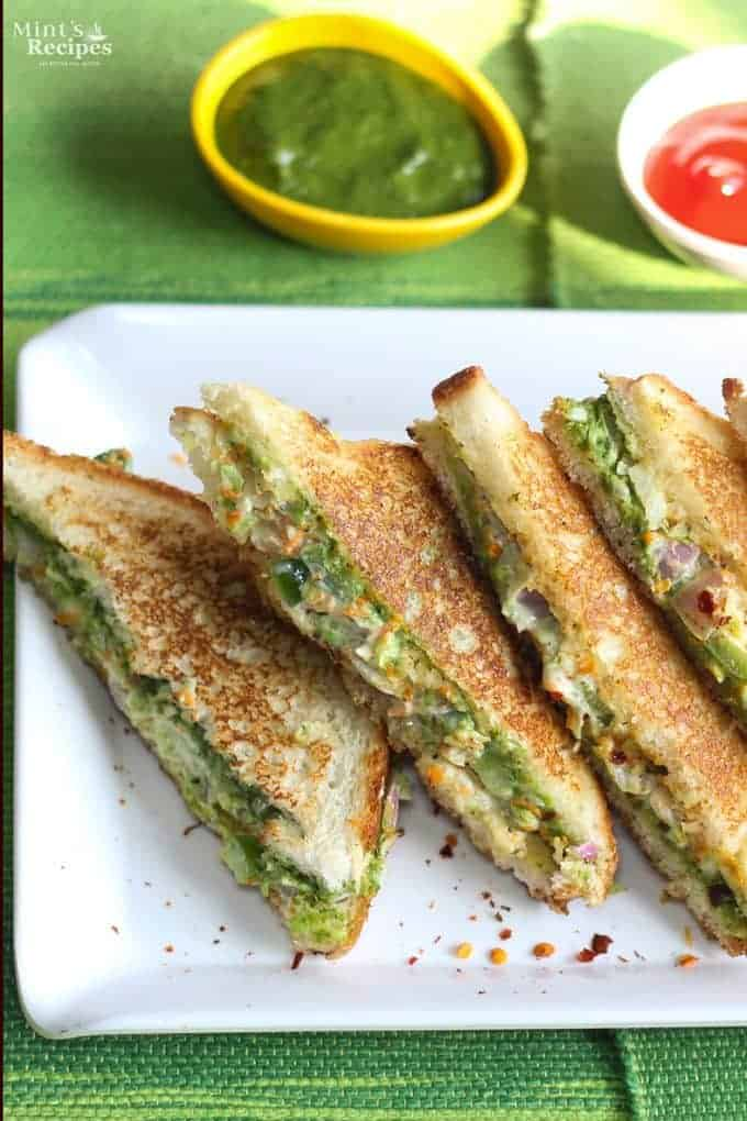Veg Mayonnaise Sandwich Recipe on a white tray with chilli flakes and some green chutney and tomato ketchup on the background  